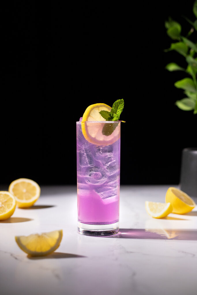 a tall purple drink garnished with a lemon wheel and a sprig of mint.