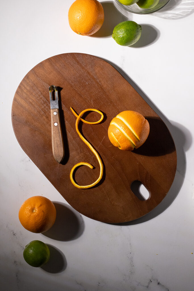 a long, thin piece of orange peel next to an orange and a channel knife.