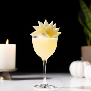 a pale yellow cocktail in a Nick and Nora glass with a pear fan garnish.