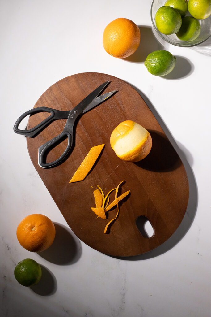 a trimmed orange peel cut into a rectangle next to scissors.