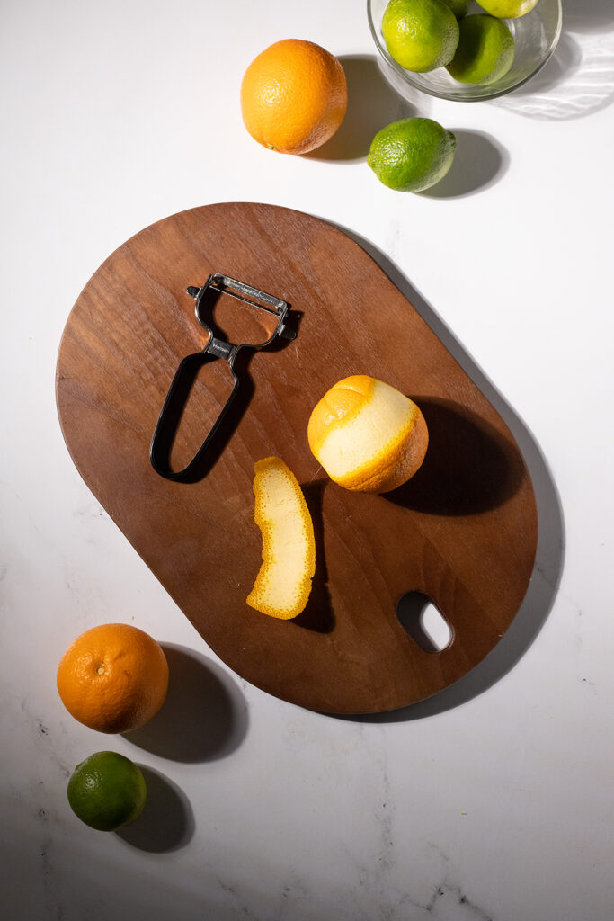 a vegetable peeler next to an orange and an orange peel