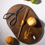 an orange peel wrapped around a wooden chopstick to make a twist.