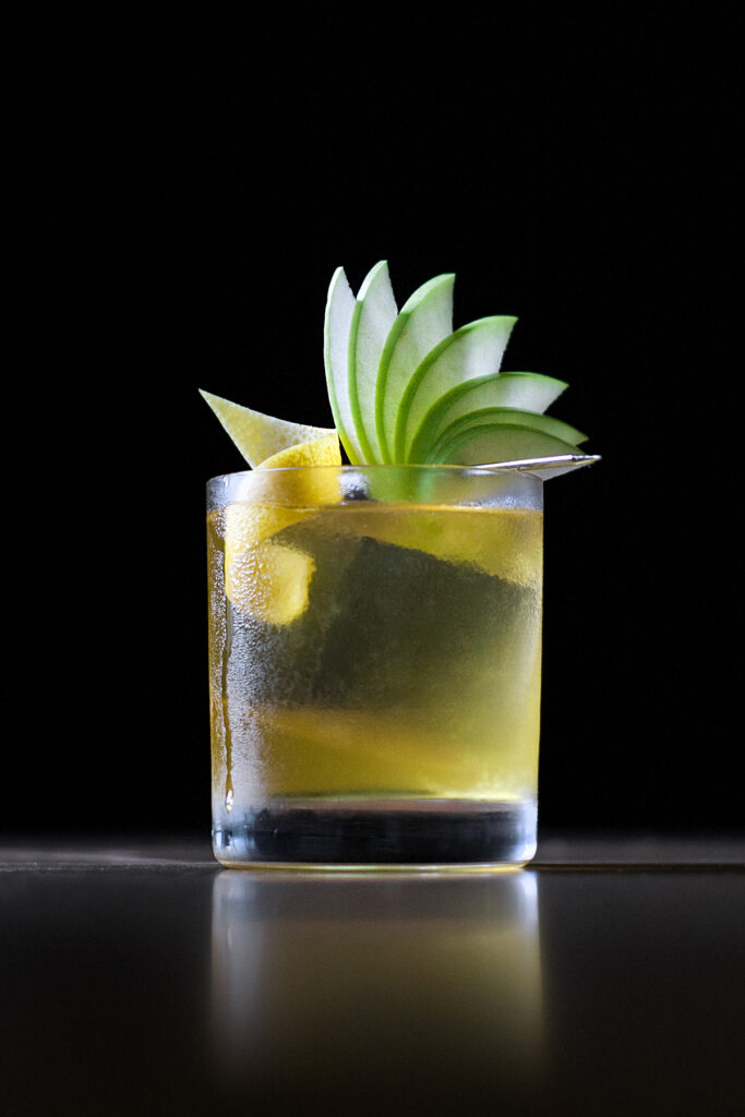 a yellow drink in a rocks glass with one clear ice cube and a fancy apple fan garnish.