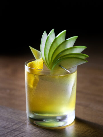 a yellow drink in a rocks glass garnished with a lemon twist and a fan of green apple slices.