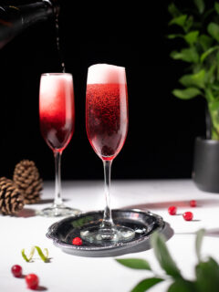 champagne flutes filled with a red cocktail with a frothy head.