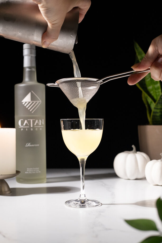 pouring a pale yellow cocktail through a fine mesh strainer into a cocktail glass.