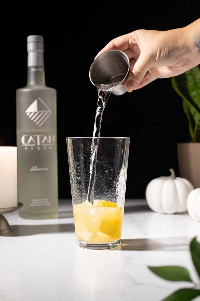 pouring pisco into a mixing glass with muddled pears.