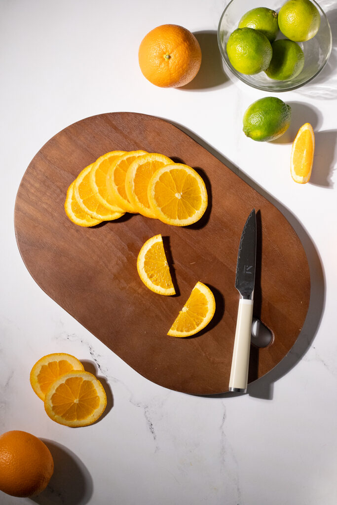 several orange wheels and two orange slices on a cutting board.